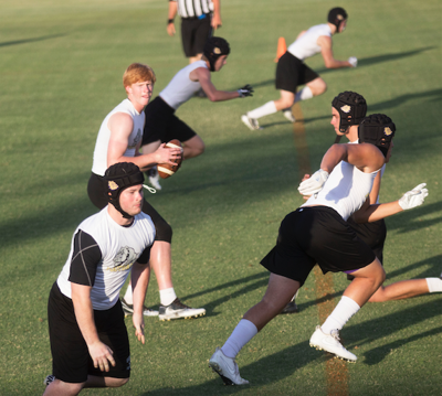 Queen Creek quarterback Devin Larsen drops back to pass during a 7-on-7 passing tournament at Arizona State University.