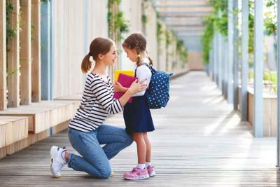 first day at school. mother leads little child school girl in first grade
