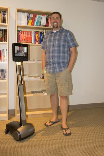 Daniel Bagley demonstrates Faithlife's telepresence robot with software developer Jeff Hart peeking in.