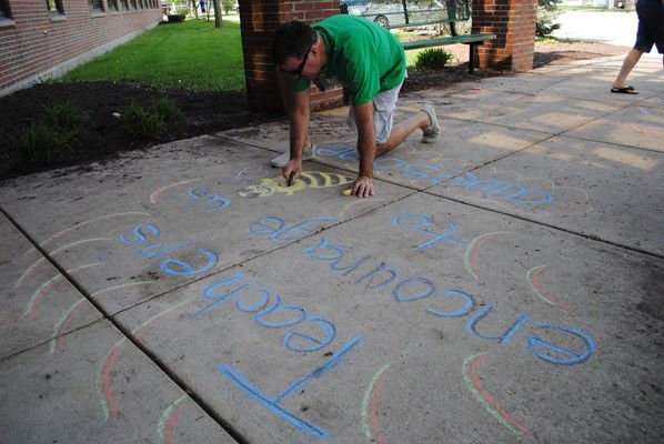 Chandler chalks the sidewalk