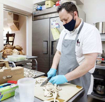 Philip Day prepares food at Root Food + Wine