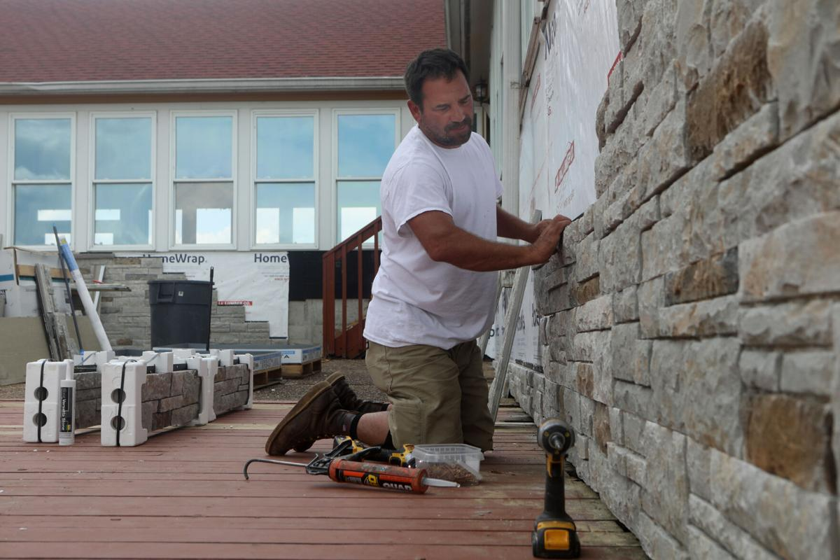 Mike Kopp installs Versetta Stone on a wall