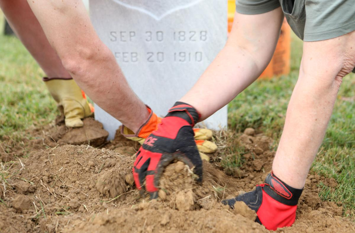 Volunteers pack sod around a headstone