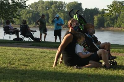 A family wears masks at Sunset on the Riverfront