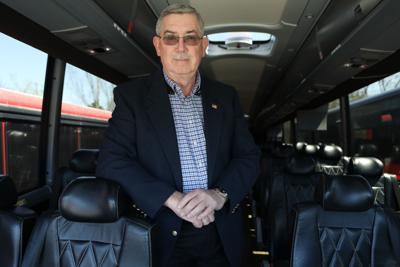 Loyd Bailie stands inside a coach bus