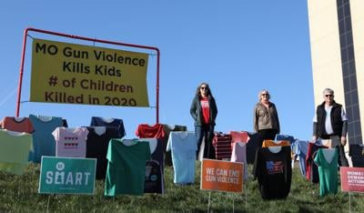 Volunteers stand next to traveling gun violence memorial