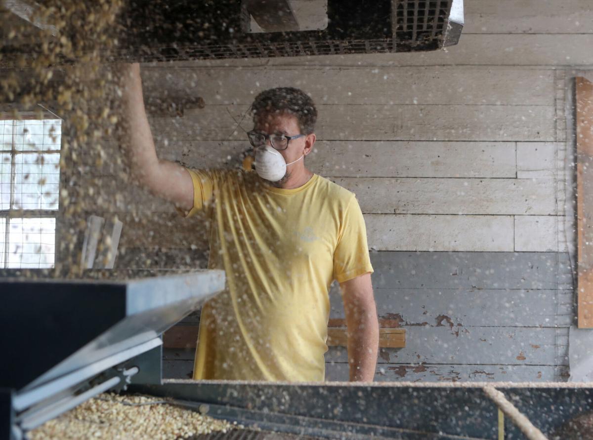 Greg Brinker pours corn into a machine