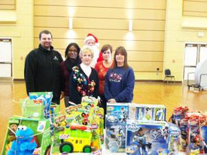 <p>Volunteers gather in front of a batch of toys purchased through the Christmas Happiness Fund to bring Christmas to approximately 300 children in the Greensville-Emporia Community.</p>