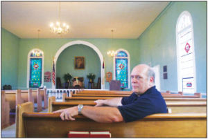 <p>Persons United Methodist Church Treasurer Mark Person takes a break inside the church. The stain glass windows are in tribute to former members from their families.</p>