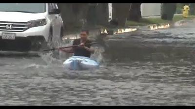 Man kayaks in flooded street in Southern California