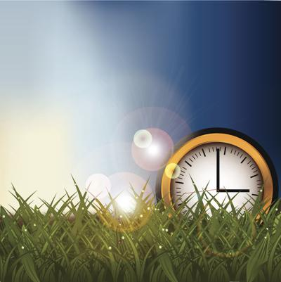 Clock in a grassy field background with copy space