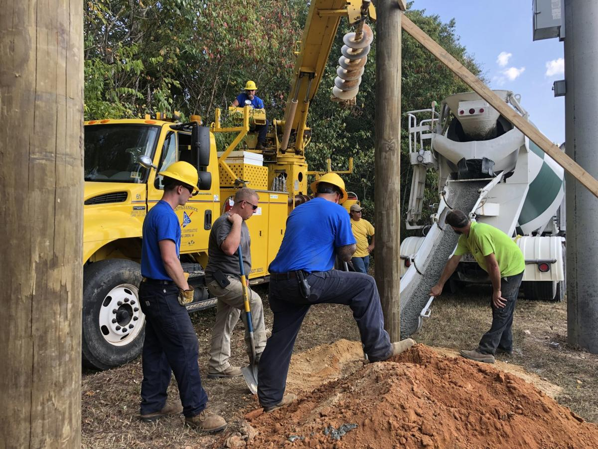 Employees of REC and G.H. Watts work to secure two utility poles for a new baseball stadium scoreboard at Caroline High School.