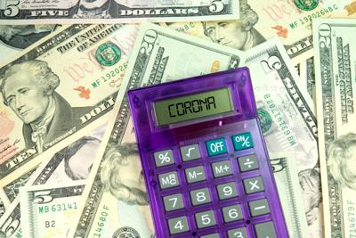 Dollar banknotes, calculators and Corona virus