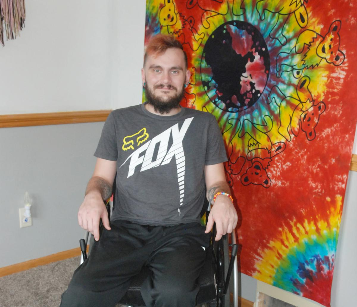 Man in chair near tie-dye wall hanging