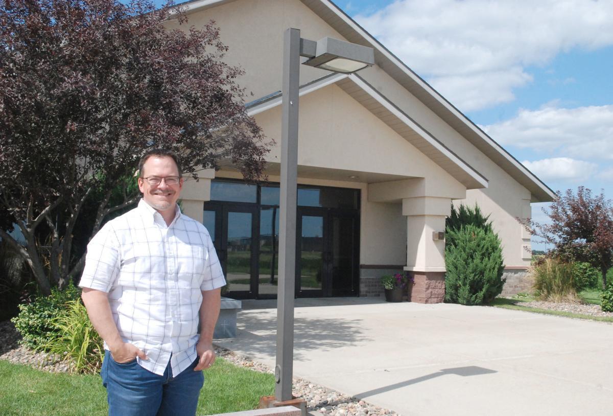 New Nazarene pastor in front of church