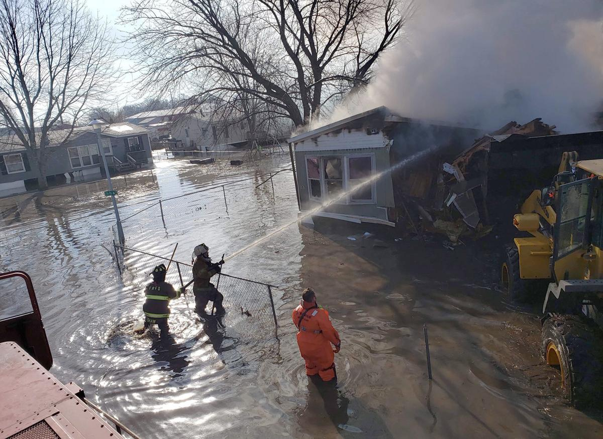 Firefighters in water spraying house