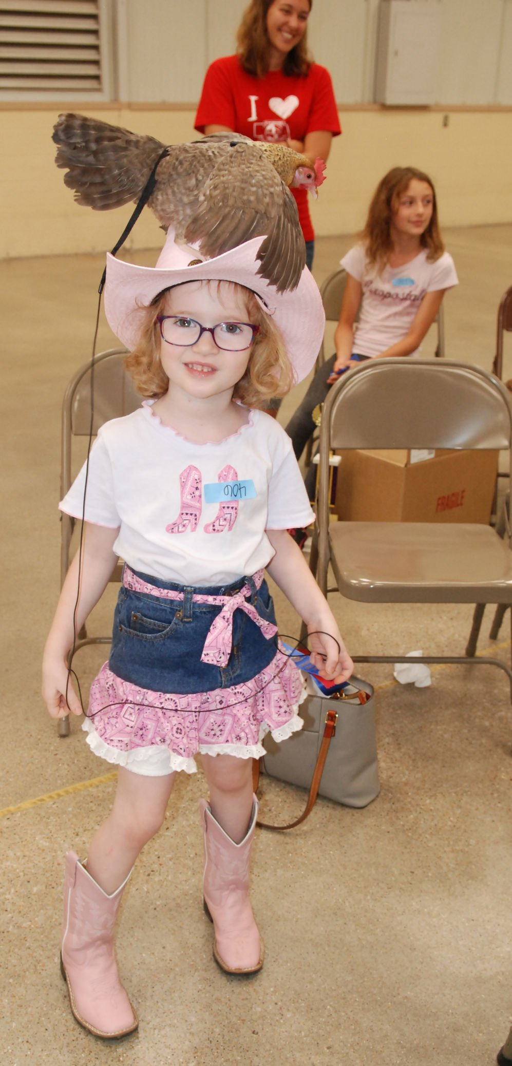 Little girl with chicken on her hat at city pet show
