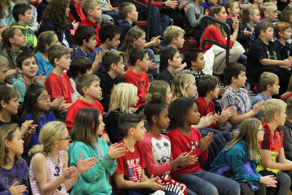 Children clapping at Veterans Day ceremony