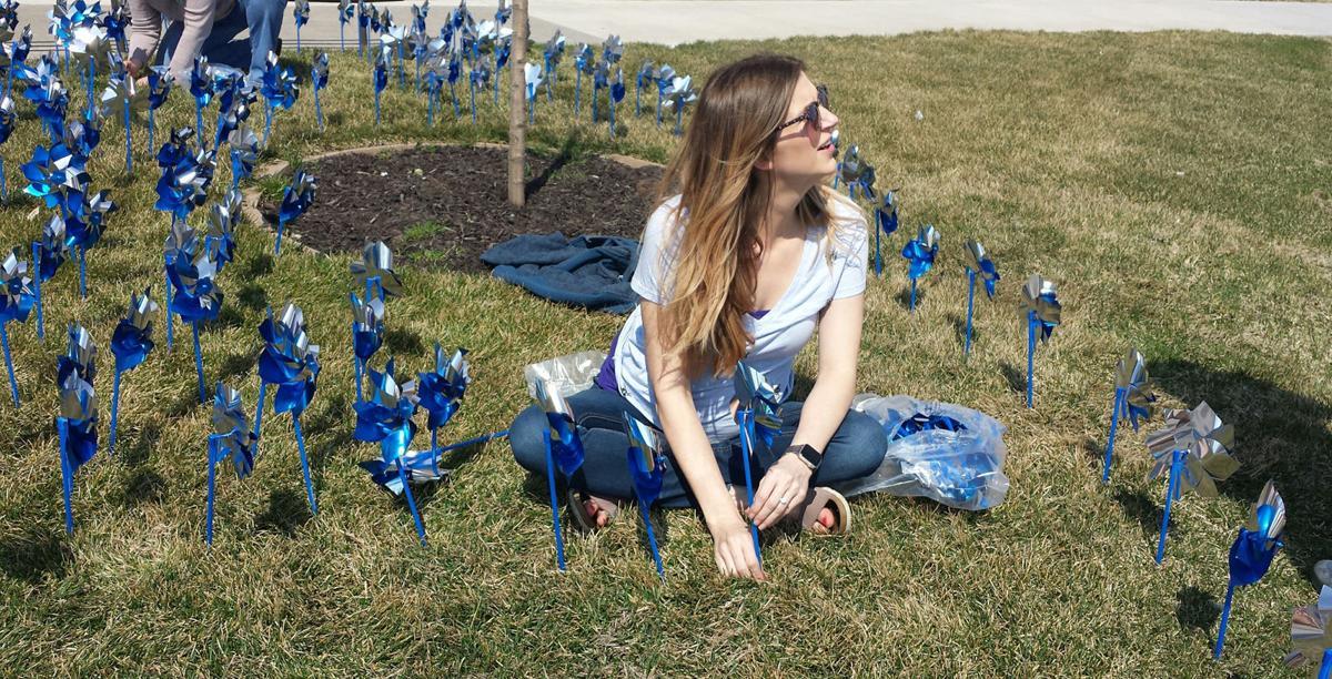 Woman sitting amid pinwheels