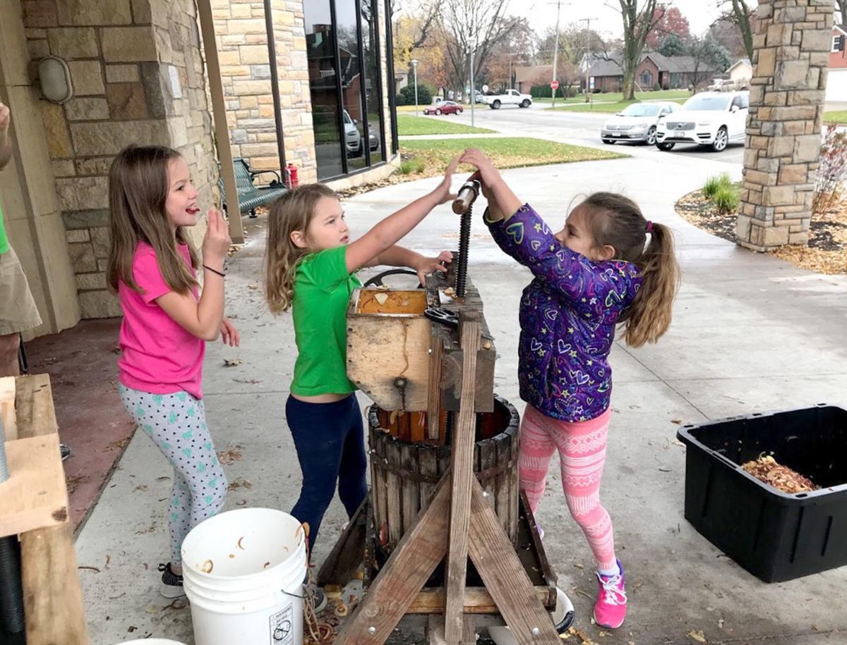 Children help make apple cider