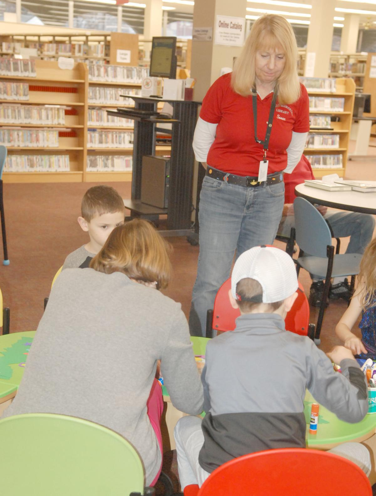 Librarian at table with kids making crafts