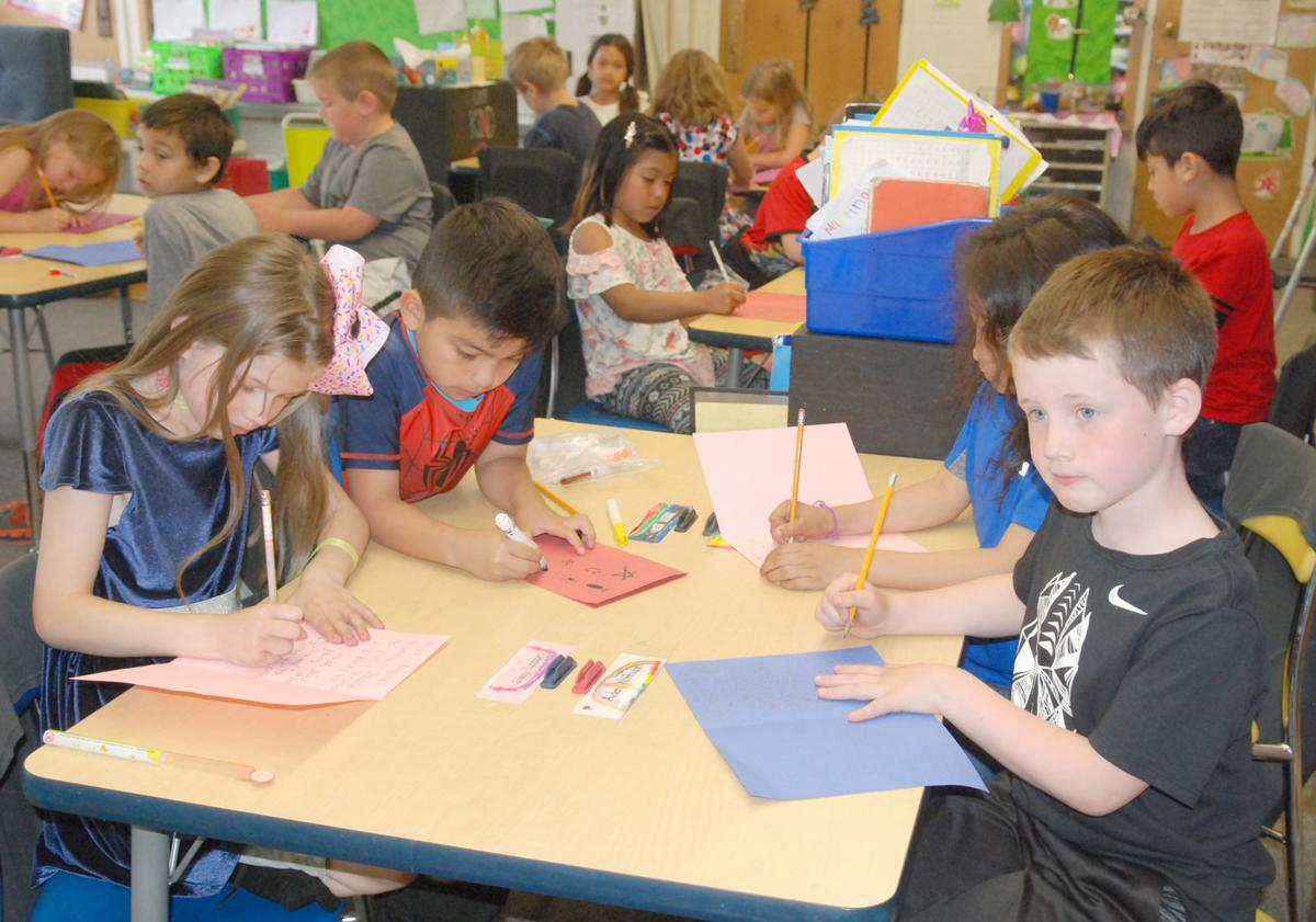 First-graders at table with cards