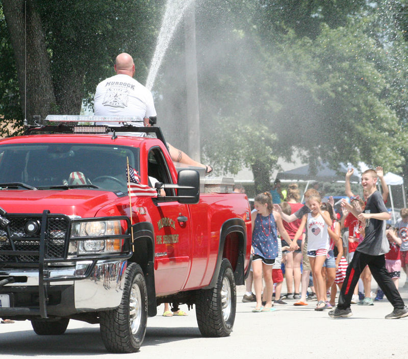Fire truck hoses water to crowd