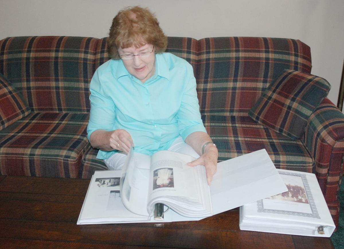 Peg looking at history books she made