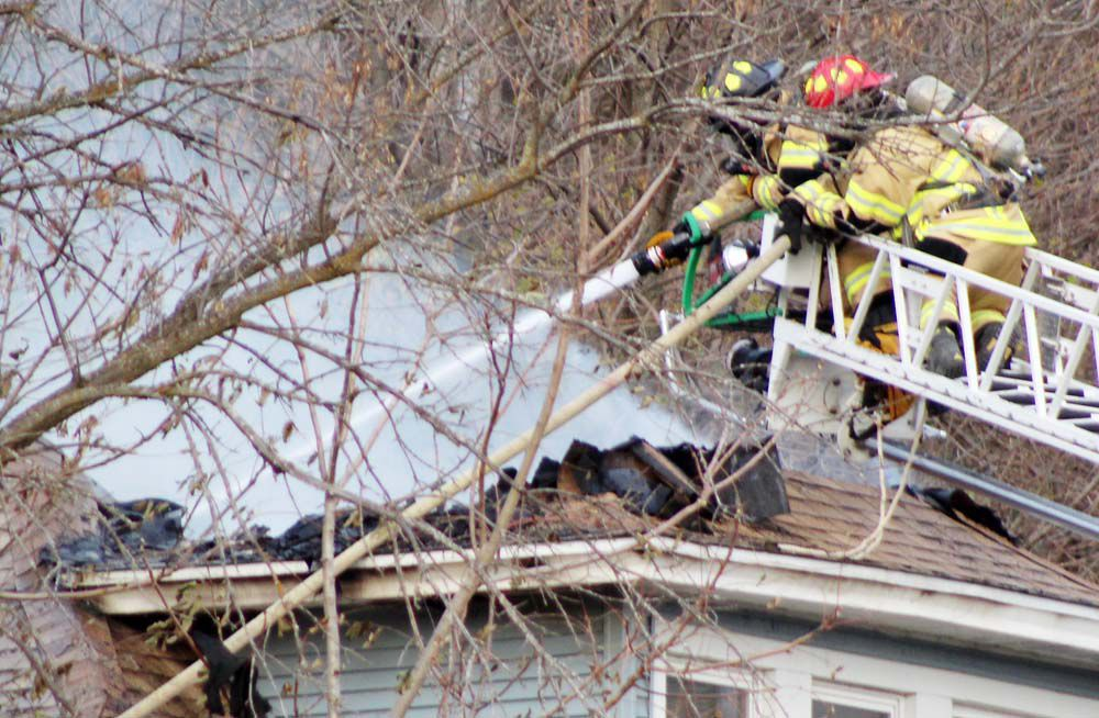 Spraying water on top of house from ladder