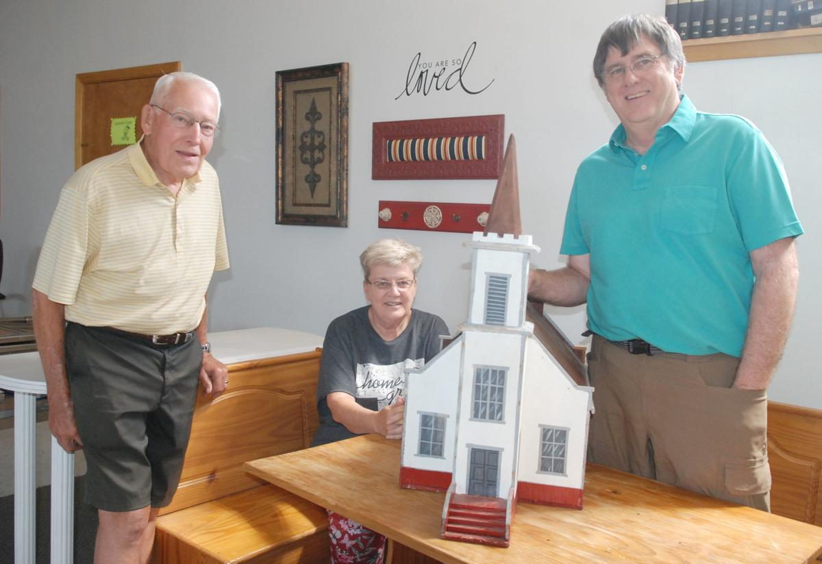 Three people and church replica