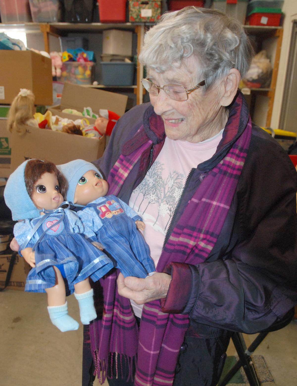 Woman looking down at set of dolls in blue