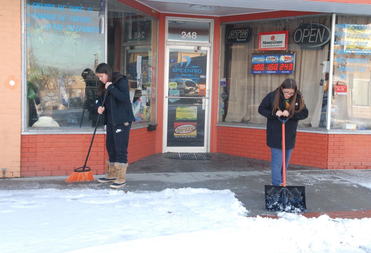 Girls clearing sidewalk in downtown Fremont
