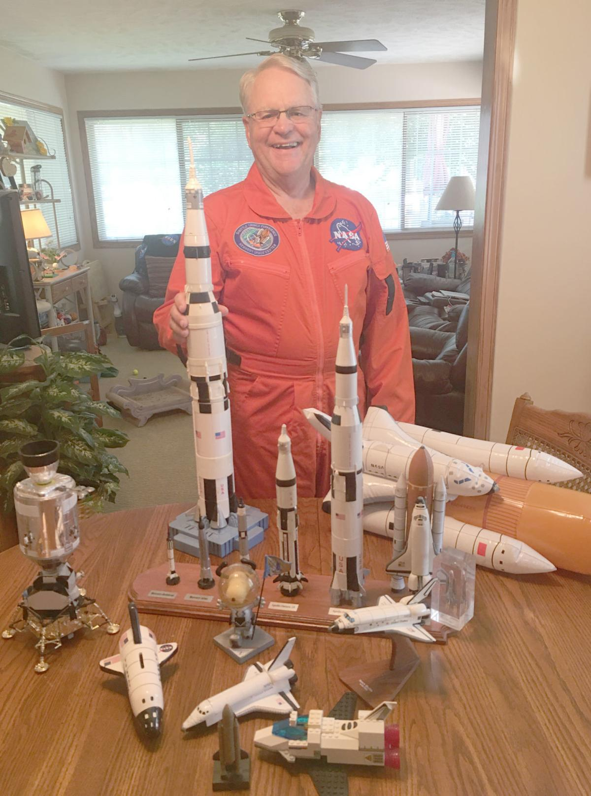 Man with models of spacecraft