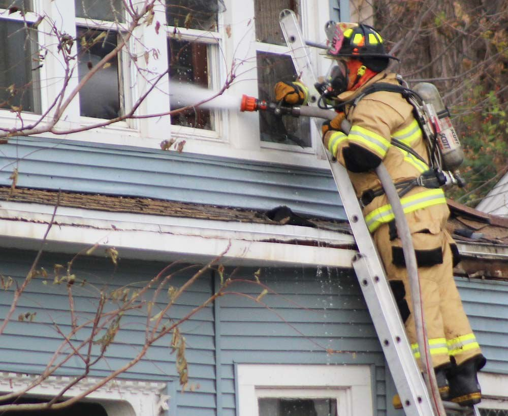Firefighter turns hose on fire through window