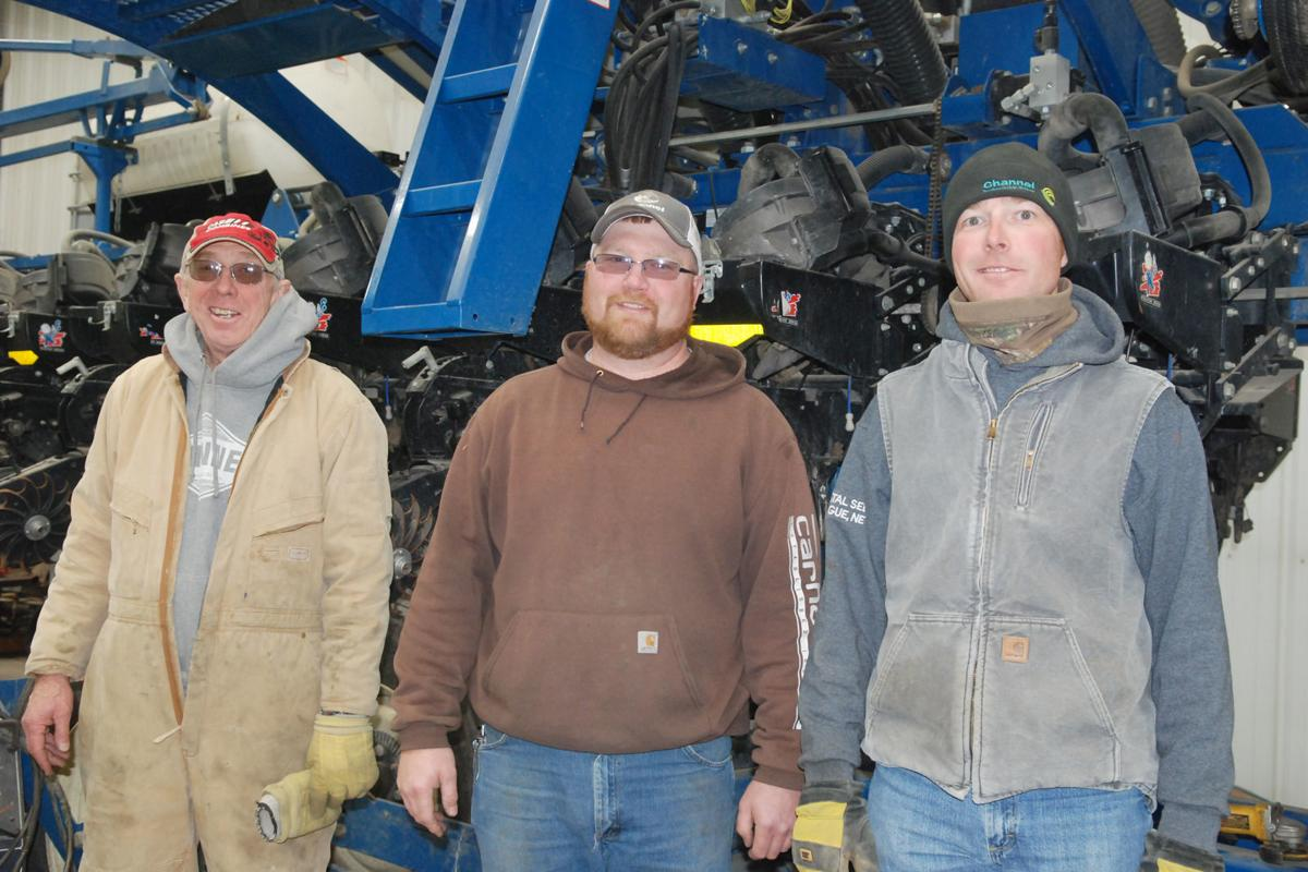 Dad and sons by machinery