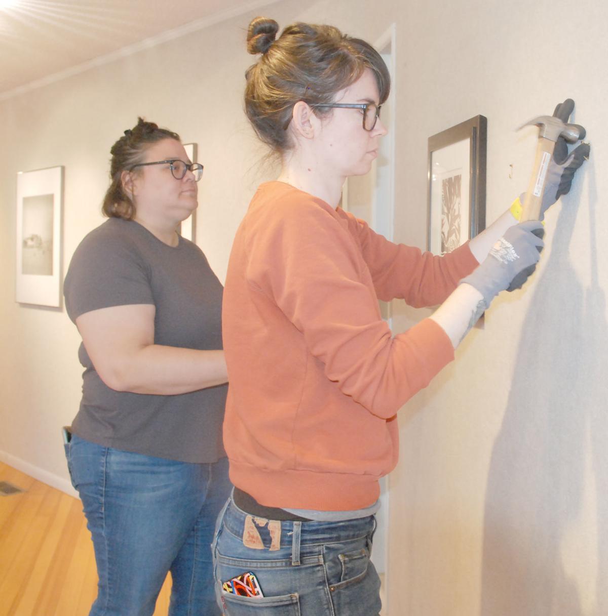 Sheldon workers hang artwork in FAAA gallery