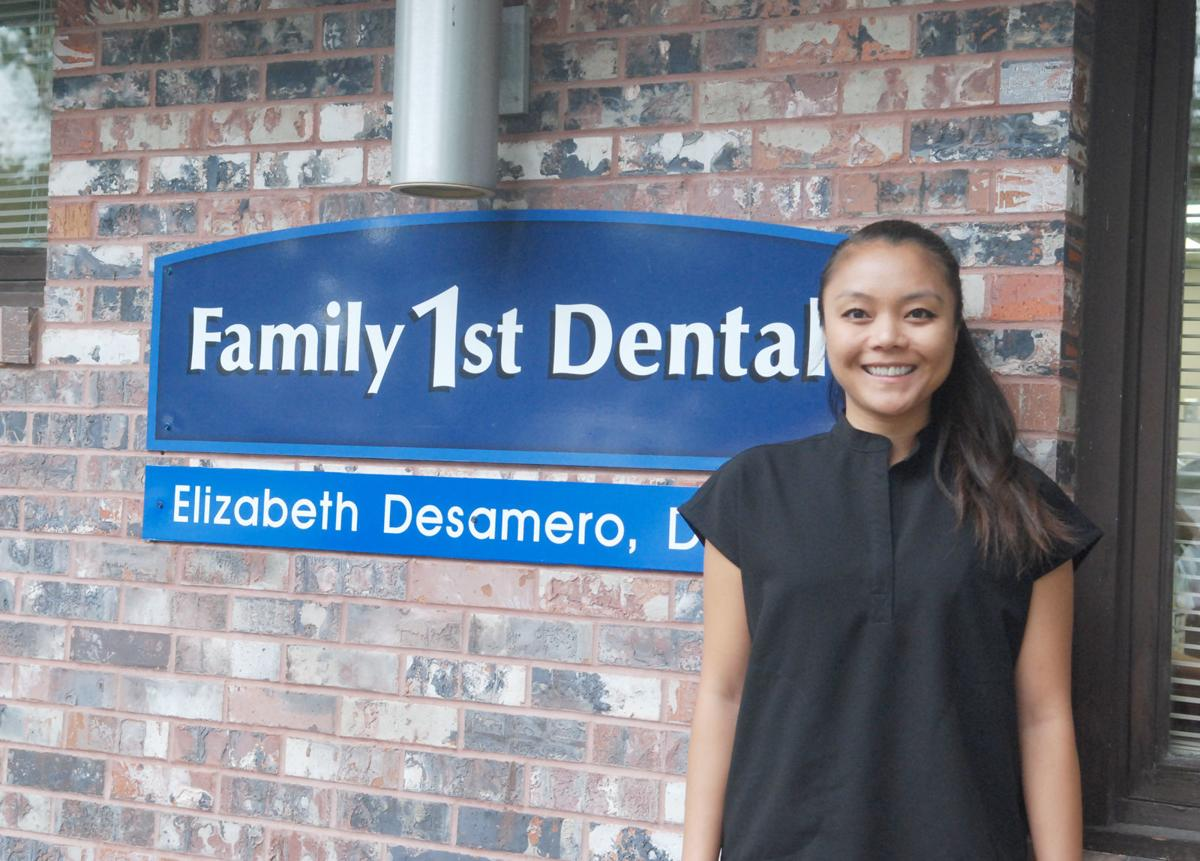 Dentist in front of sign