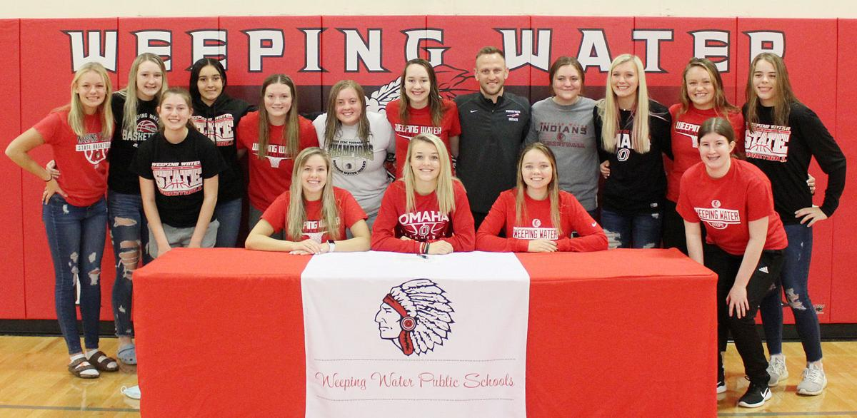 Girls basketball team smiles at signing ceremony