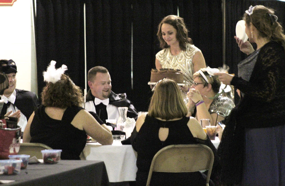 Alicia Garbers delivers cake to table during auction