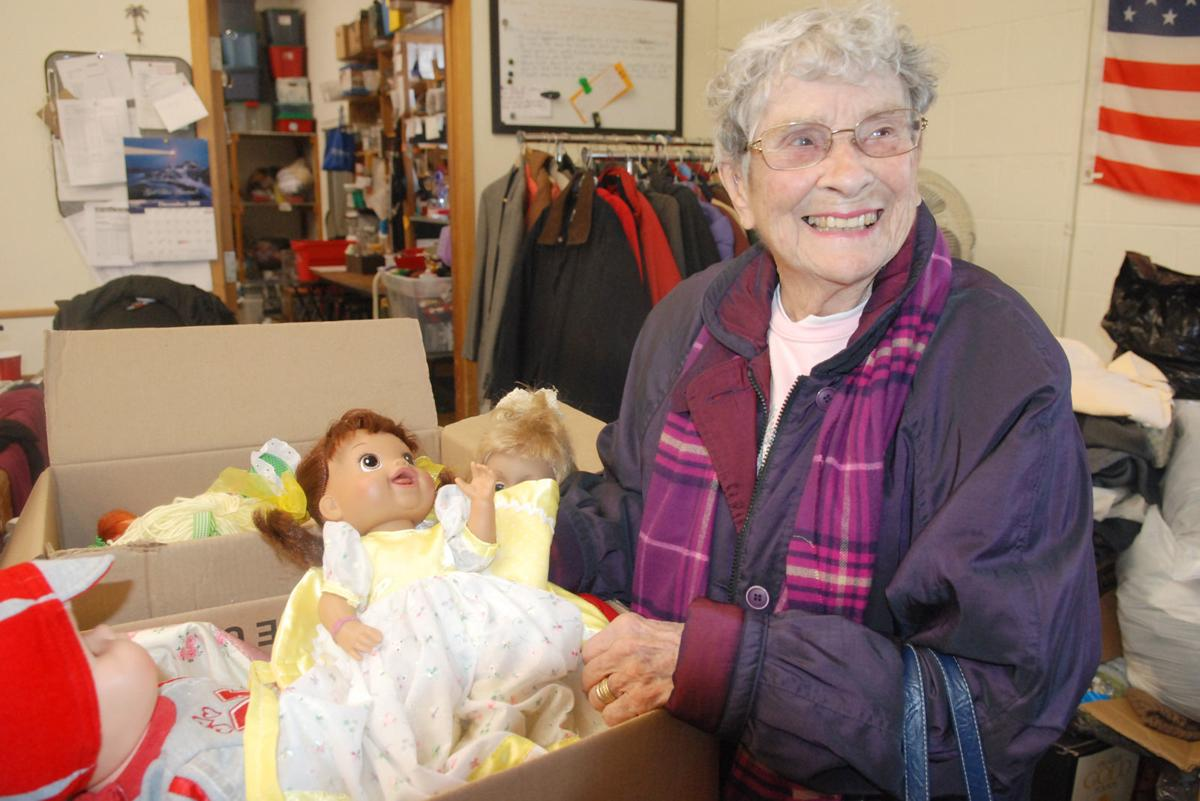 Smiling woman with doll with yellow and white outfit