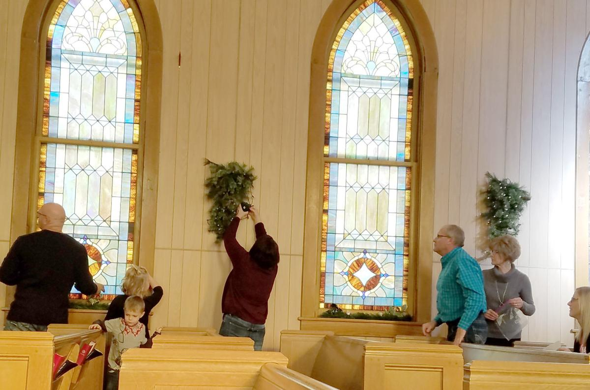 People hanging greens in church