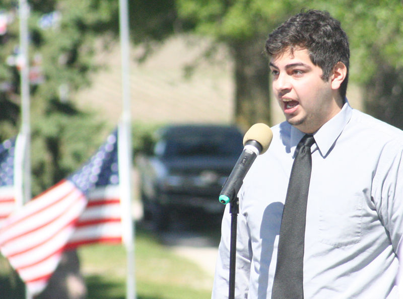 Isaiah Kluver sings with flags in background at Elmwood