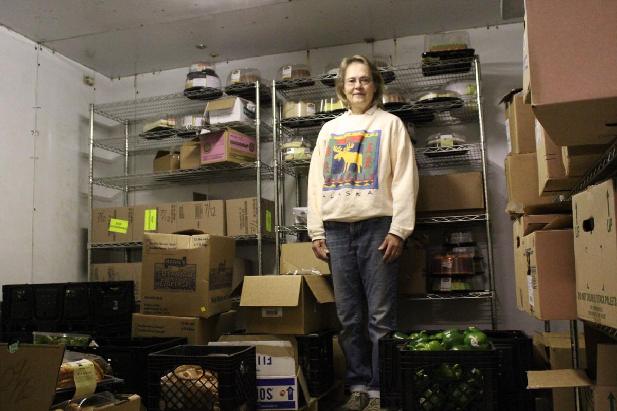 Palmer Food Bank Director Jeanne Borega stands among donated items in the walk-in cooler