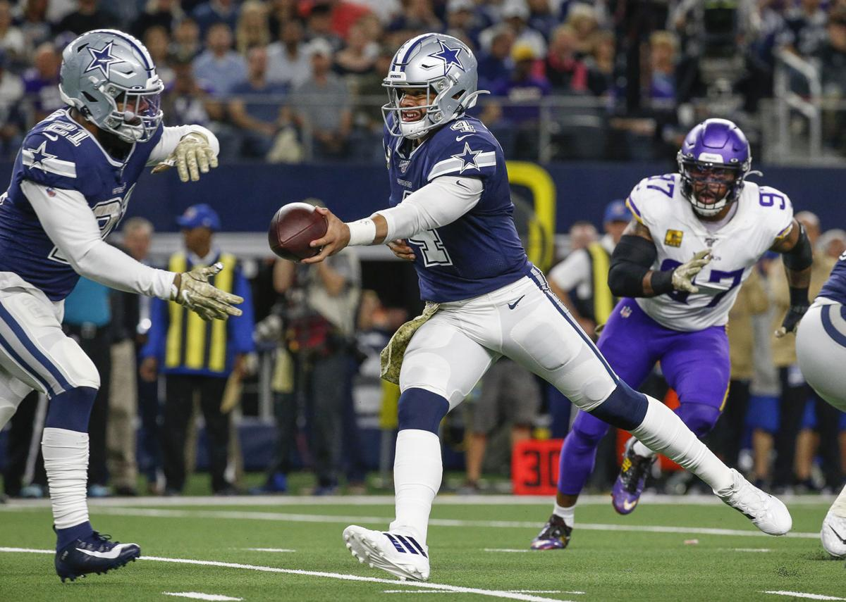 Dallas Cowboys quarterback Dak Prescott (4) hands off to running back Ezekiel Elliott (21) during the first quarter on Sunday, Nov. 10, 2019 at AT&T Stadium in Arlington, Texas.