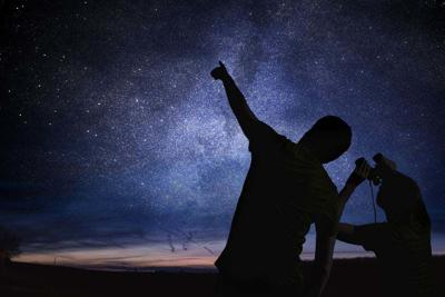 Silhouettes of people observing stars in night sky. Astronomy co