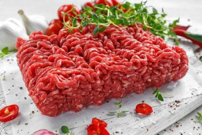 Fresh Raw Beef Minced Meat with salt, pepper, chilli and fresh thyme on white board.
