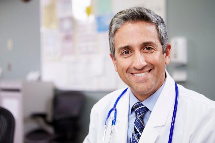 Portrait Of Doctor Working At Nurses Station