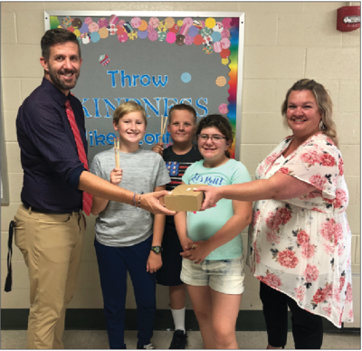 Gladwin Junior High School Principal Dave Mausolf and three Junior High Students receive the pencils from Andrea Lane.