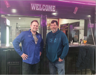 Manager Tommy Spencer (left) and owner Joe Lancaster (right) stand in front of the drop down bar at 18 Taps LLC in Beaverton.