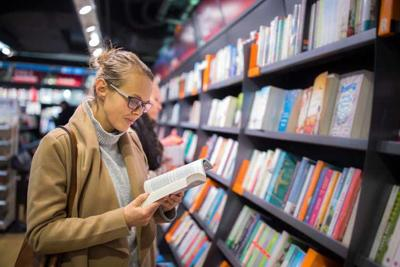 Pretty, young female choosing a good book to buy in a bookstore